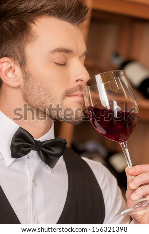 Confident sommelier. Side view of confident young sommelier holding a wine glass and keeping his eyes closed  - stock photo
