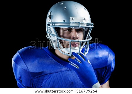 Confident sportsman holding helmet while looking away against black background