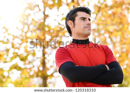 Confident sportsman portrait in nature. Handsome male athlete idly looking. Trees on copy space background. - stock photo