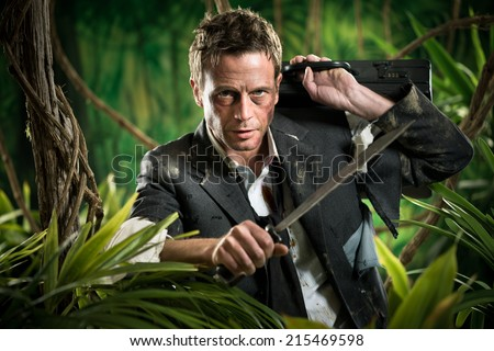 Confident strong businessman dealing with jungle dangers, holding a machete. - stock photo
