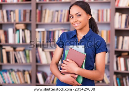 Confident student. Beautiful female African student holding books and smiling while standing in library - stock photo