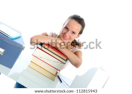 Confident student with textbooks Smiling confident student sitting at her desk leaning on a tall stack of textbooks, angled view against white