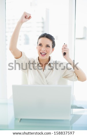 Confident stylish brunette businesswoman raising her fist in bright office