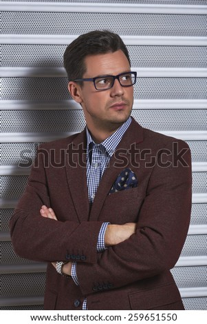 Confident stylish handsome gentleman posing with crossed arms, wearing spectacles, checked shirt and brown suit jacket with handkerchief in pocket over grey metal textured background. - stock photo