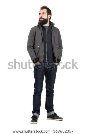 Confident stylish hipster wearing jacket over hooded sweatshirt looking away with hands in pockets. Full body length portrait isolated over white studio background.
