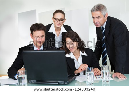 Confident successful business team of diverse executives posing in an office together smiling happily at the camera