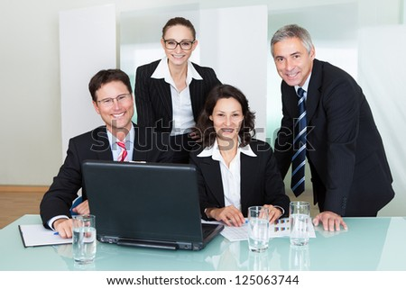 Confident successful business team of diverse executives posing in an office together smiling happily at the camera - stock photo