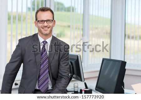 Confident successful male business executive relaxing on the edge of his desk in front of a view window overlooking countryside - stock photo