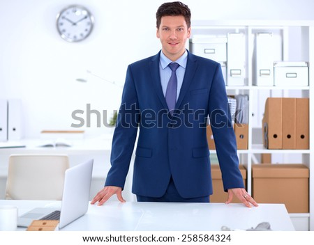 Confident successful young businessman leaning arms on his desk isolated - stock photo