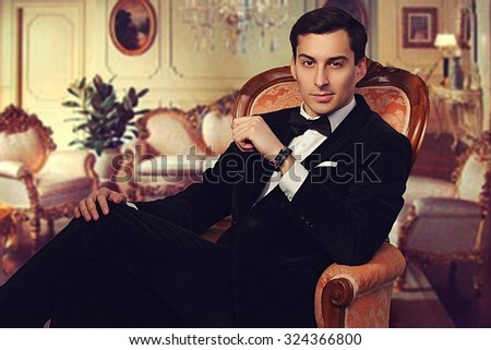 Confident successful young handsome man businessman in elegant suit with bow tie sitting on vintage armchair in luxurious living room. Manhood. Male beauty. Fashion model studio shot. Italian style.  - stock photo