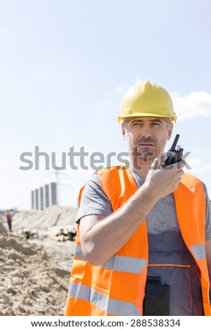 Confident supervisor using walkie-talkie at construction site against sky - stock photo
