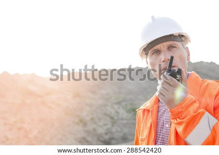 Confident supervisor using walkie-talkie on construction site against clear sky - stock photo
