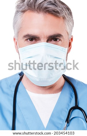 Confident surgeon. Mature grey hair doctor in surgical mask looking at camera while standing isolated on white