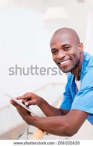 Confident surgeon. Side view of thoughtful young African doctor in blue uniform working on digital tablet and smiling while leaning at handrail - stock photo