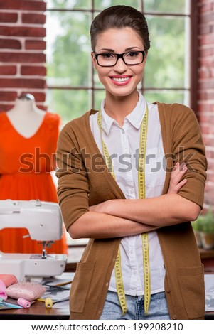 Confident tailor. Beautiful young female tailor holding scissors and smiling at camera while mannequin standing in the background - stock photo