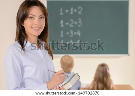 Confident teacher. Cheerful young teacher smiling at camera while pupils studying on background