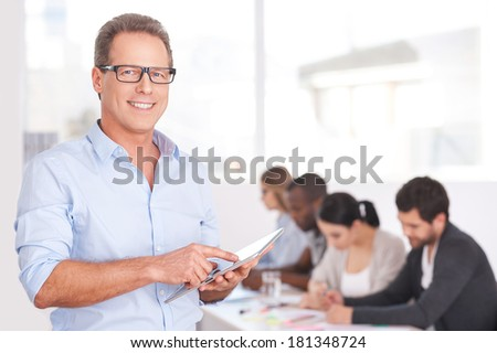 Confident team leader. Confident young man in glasses working on digital tablet and smiling while people working on background - stock photo