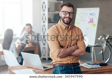 Confident team leader. Confident young man keeping arms crossed and looking at camera with smile while his colleagues working in the background - stock photo