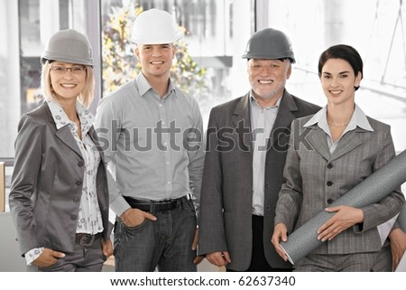 Confident team of architects wearing hardhat, holding plan, smiling at camera.?