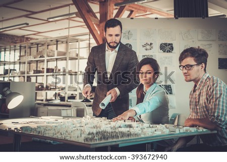 Confident team of engineers working together in a architect studio. - stock photo