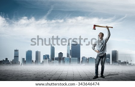 Confident teenager boy holding axe in hand above head