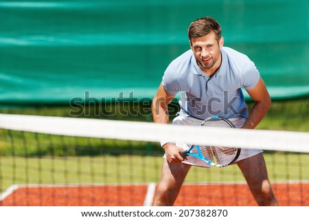 Confident tennis player. Handsome young man in polo shirt holding tennis racket and smiling while standing on tennis court - stock photo