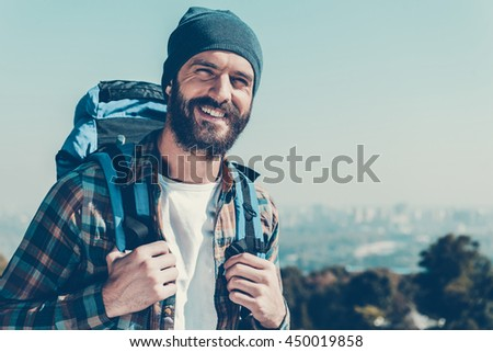 Confident traveler. Handsome young man carrying backpack and looking at camera with smile while standing in the nature - stock photo