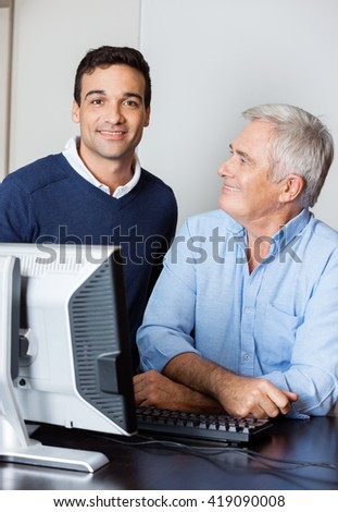 Confident Tutor With Senior Student In Computer Lab - stock photo