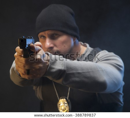 Confident Undercover Law Enforcement Special Agent with weapon. Focus is on the gun.