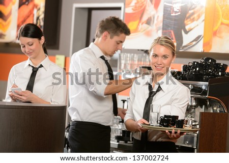 Confident waitresses and waiter working in bar serving drinks - stock photo