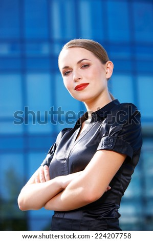 Confident White Office Girl with Crossed Arms in Sexy Black Blouse Looking at Camera. Isolated on Huge Building Glass Walls.
