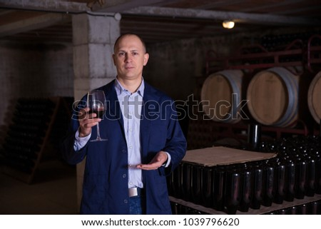 Confident winemaker inviting to wine cellar, offering glass of red wine for tasting