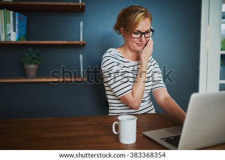 Confident woman at home office talking at the phone while using laptop - stock photo