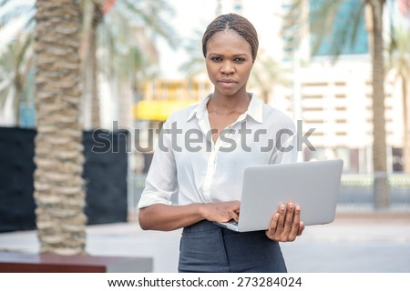 Confident woman. Confident businesswoman African businessman standing on the street and holding a laptop in the hands of Dubai downtown among the skyscrapers