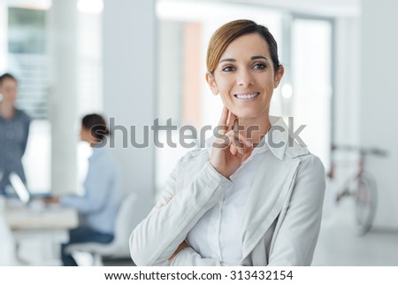 Confident woman entrepreneur posing in her office and smiling at camera, success and women empowerment concept - stock photo