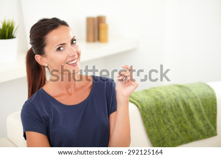 Confident woman in blue shirt toothy smiling at the camera while sitting indoors - copy space - stock photo