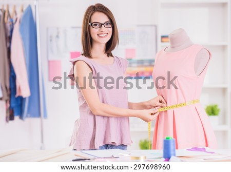 Confident woman in glasses measuring pink dress, looking at camera and smiling.