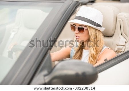Confident woman in sunglasses and hat driving by cabriolet. - stock photo