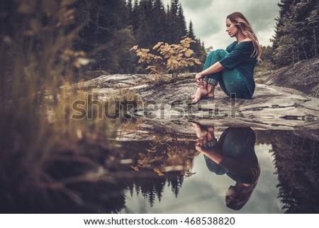 Confident woman posing near pond with mountain forest on the background.