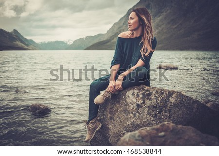 Confident woman posing on the shore of a wild lake, with mountains on the background.
