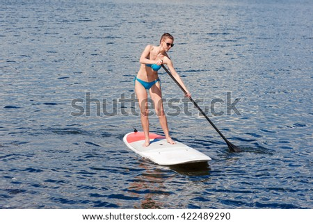confident woman swimsuit standing with a paddle on the surfboard