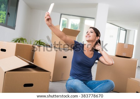 Confident woman taking a selfie with her mobile in her new house, she is sitting on the floor with lots of carton boxes