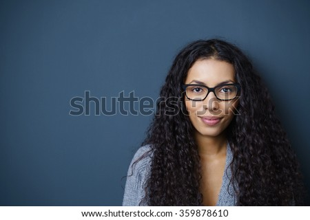 confident woman with glasses looking at camera standing against dark grey background in the studio - stock photo