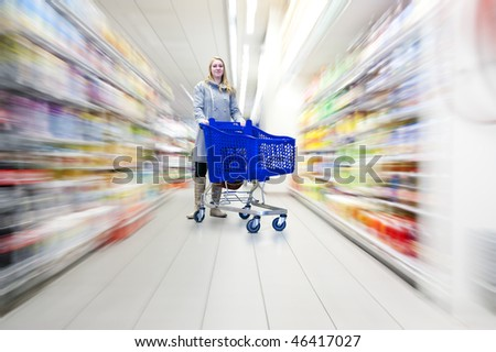 Confident woman with her shopping cart in a supermarket, doing groceries - what to choose