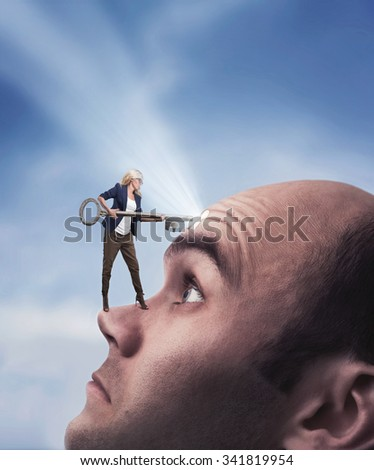 Confident woman with key on the man's face with keyhole - stock photo