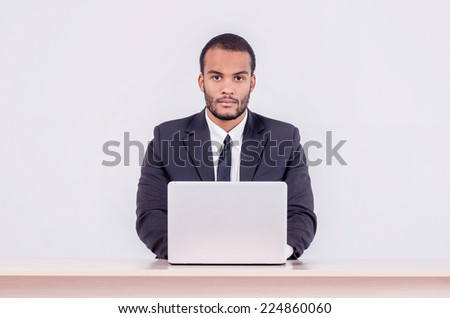 Confident worker business. Smiling African businessman sitting at the table and typing a business plan on a laptop while a businessman sitting at a desk and smiling at the camera on a gray background - stock photo