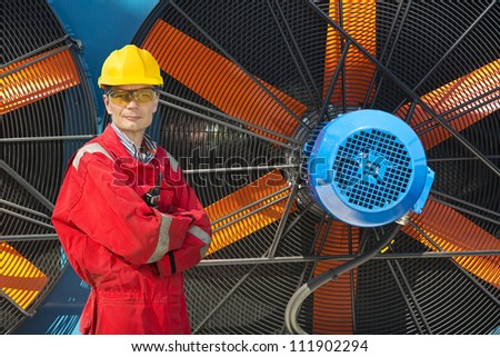 Confident worker with coveralls, hard hat and safety glasses in front of a couple of huge industrial fans - stock photo