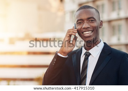 Confident young African businessman smiling while on his phone - stock photo