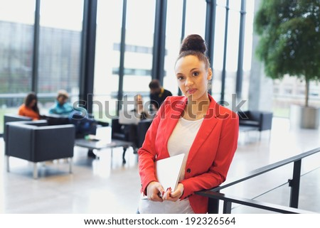 Confident young afro american woman holding a laptop standing by a railing looking at camera. Young businesswoman in office with people sitting in background. - stock photo