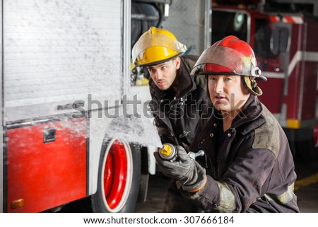 Confident young and mature firemen spraying water during training at fire station - stock photo